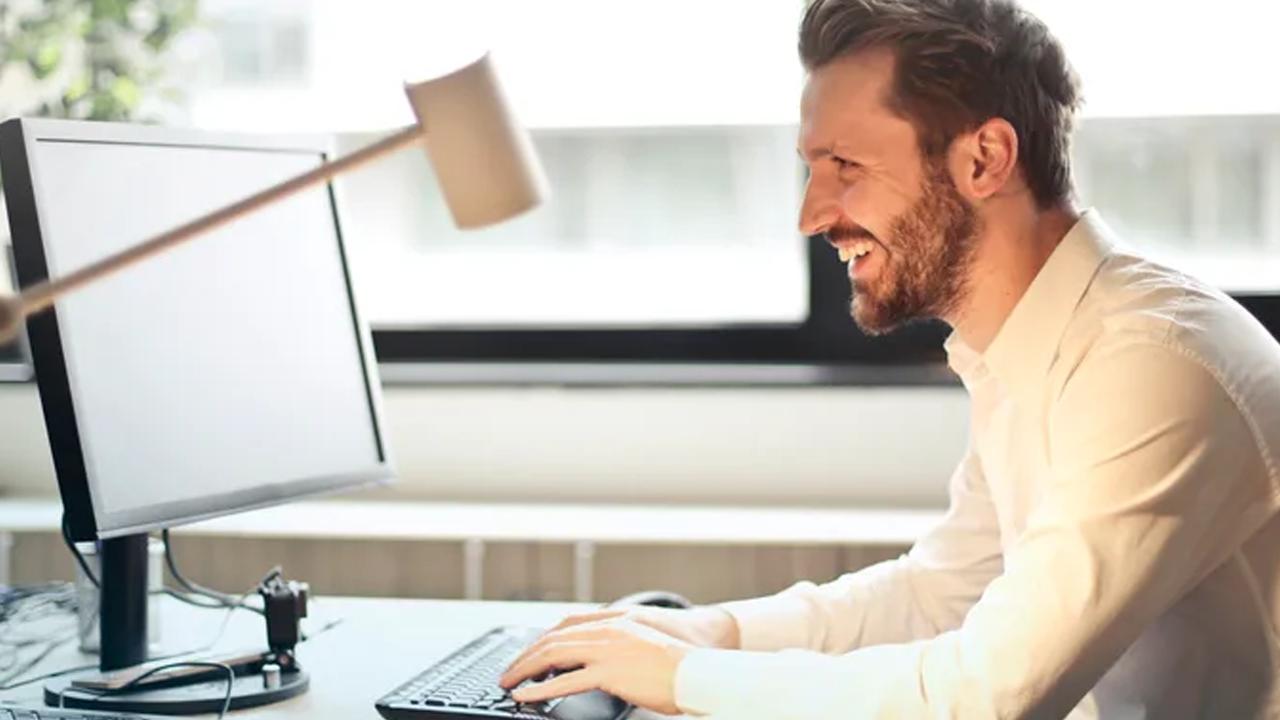 Lachende man achter computer